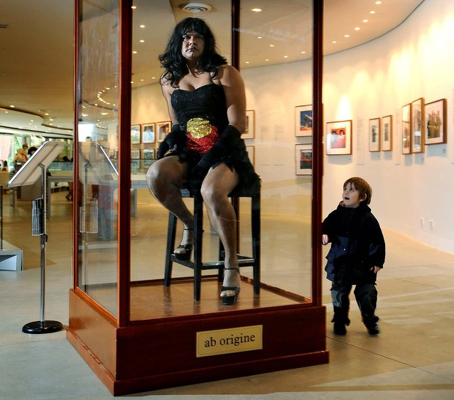 "Constantina Bush, an alter-ego of male Aboriginal performer Kamahi King, poses in a museum display case in ""Jacky Jacky in the Box"" at a preview of a new Aboriginal exhibition titled ""20 Years: Bold. Black. Brilliant"". at the Melbourne Museum. The performance art installation challenges audiences to reconsider their perceptions of Indigenous Australia as an anthropological curiosity. (Photo by William West/AFP/Getty Images)"