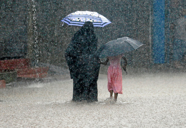 A woman walks with a girl along a flooded road in the heavy rains in Malwana, Sri Lanka on May 23, 2018. (Photo by Dinuka Liyanawatte/Reuters)