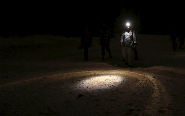 A hiker uses a flash light to see the ground as he walks in the Wadi Rum area in South Sinai, Egypt, November 20, 2015. (Photo by Asmaa Waguih/Reuters)