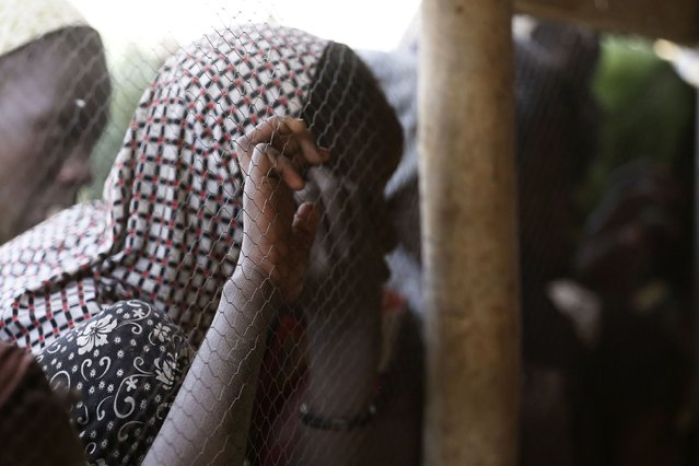 A young woman refugee from Nigeria looks through a fence in Ngouboua, January 19, 2015. Refugees fleeing attacks by Islamist militant group Boko Haram continued to cross the border into neighbouring Chad on Monday. (Photo by Emmanuel Braun/Reuters)