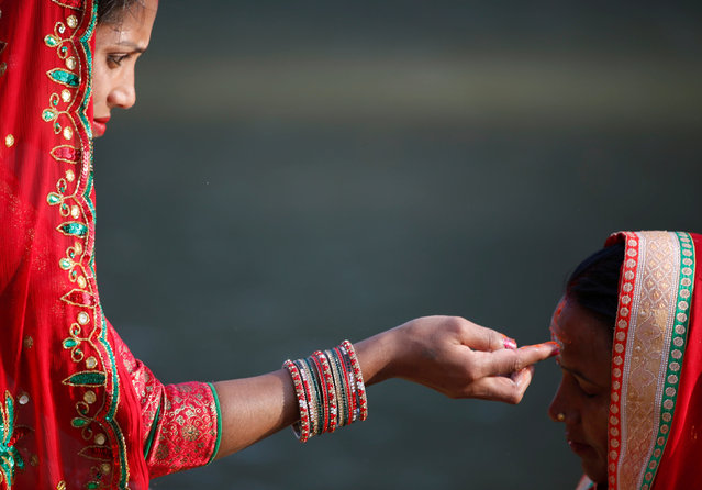 """A devotee (L) offers tika to her friend during the """"Chhat"""" festival at Bagmati River in Kathmandu, Nepal November 6, 2016. (Photo by Navesh Chitrakar/Reuters)"""