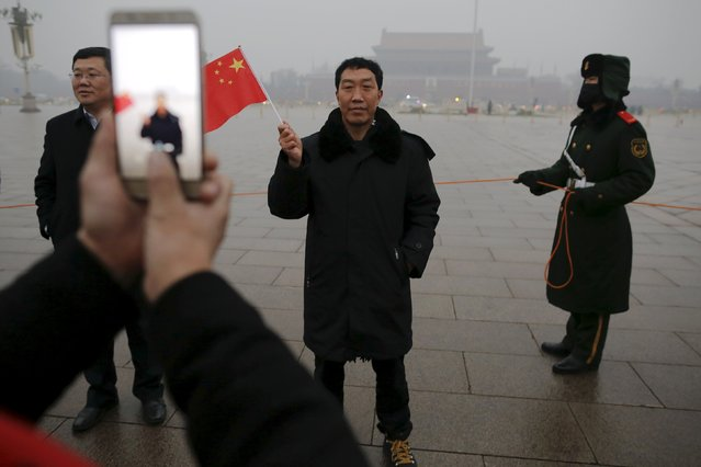 "A man has his picture taken just after a flag-raising ceremony amid heavy smog at the Tiananmen Square, after the city issued its first ever ""red alert"" for air pollution, in Beijing December 9, 2015. (Photo by Damir Sagolj/Reuters)"