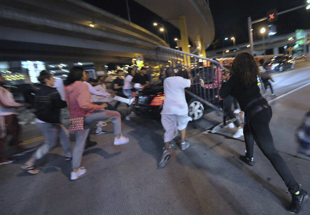 In this Friday, June 22, 2018 photo, a car runs aggressively through a crowd of protesters on the north side on Tony Dorsett Way at West General Robinson Street in Pittsburgh. Protesters upset that some were nearly injured by the vehicle pursued it throwing water bottles and a heavy metal traffic barrier. The protest was in response to the fatal police shooting of 17-year-old Antwon Rose Jr. on Tuesday, who was shot fleeing a traffic stop in Pittsburgh. (Photo by Andrew Stein/Pittsburgh Post-Gazette via AP Photo)