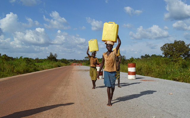 Girls carry water on a road leading past the village where Alfred Olango's family once lived in Koc Angako Nwoya, Gulu, Uganda September 29, 2016. (Photo by James Akena/Reuters)