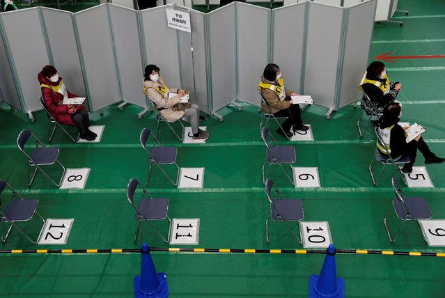 Participants in a mock inoculation exercise wait their turn, as Japan prepares for coronavirus disease (COVID-19) vaccination campaign, at a college gym in Kawasaki, Japan, January 27, 2021. (Photo by Kim Kyung-Hoon/Reuters)
