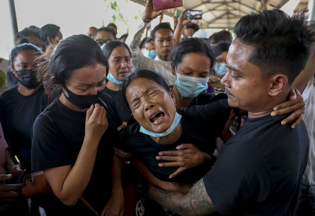 Thida Hnin cries during the funeral of her husband Thet Naing Win at Kyarnikan cemetery in Mandalay, Myanmar, Tuesday, February 23, 2021. Thet Naing Win was shot and killed by Myanmar security forces during an anti-coup protest on Saturday, Feb. 20. Thousands gather at Kyarnikan cemetery in Mandalay for the funeral. (Photo by AP Photo/Stringer)