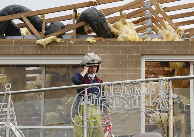 A fireman assesses the damage to a house after its roof was torn off during a tornado in the Sydney suburb of Kurnell, December 16, 2015. (Photo by Jason Reed/Reuters)