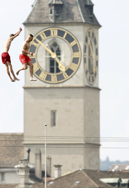 Two men jump from a 10 metre (32ft) high public diving platform into Lake Zurich during a sunny summer day in Zurich July 25, 2013. In the background is seen St. Peter church. (Photo by Arnd Wiegmann/Reuters)