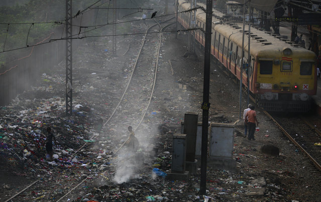 A local train moves past a burning garbage dump at a local train station in Mumbai, India, Monday, January 26, 2015. (Photo by Rafiq Maqbool/AP Photo)