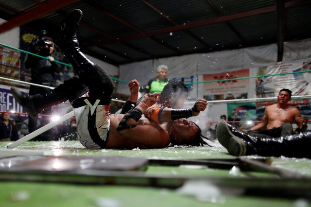 Wrestler known as Gio Malkriado (top) smashes a fluorescent tube on wrestler Ciclope during an extreme wrestling fight at a temporary wrestling ring inside a car wash in Tulancingo Hidalgo, Mexico October 8, 2016. (Photo by Carlos Jasso/Reuters)