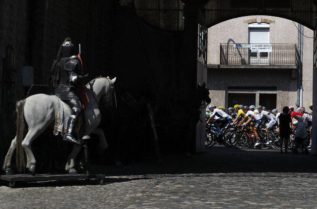 The pack with Britain's Geraint Thomas, wearing the overall leader's yellow jersey rides past a Horse statue during the sixteenth stage of the Tour de France cycling race over 218 kilometers (135.5 miles) with start in Carcassonne and finish in Bagneres-de-Luchon, France, Tuesday, July 24, 2018. (Photo by Peter Dejong/AP Photo)
