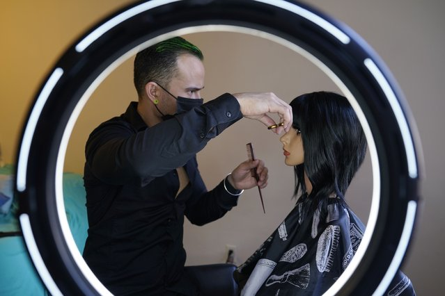 Venezuelan immigrant and hair stylist Gustavo Acosta, 36, trims a model's hair in his apartment, Tuesday, March 9, 2021, in New York. Acosta cheered when he learned that the Biden government had ordered temporary protected status for Venezuelans. He arrived in the U.S. in March 2019, illegally crossing the border with Mexico and turning himself over to authorities at a port of entry. He was detained for 13 months and applied for asylum but was denied and ordered deported. (Photo by Kathy Willens/AP Photo)