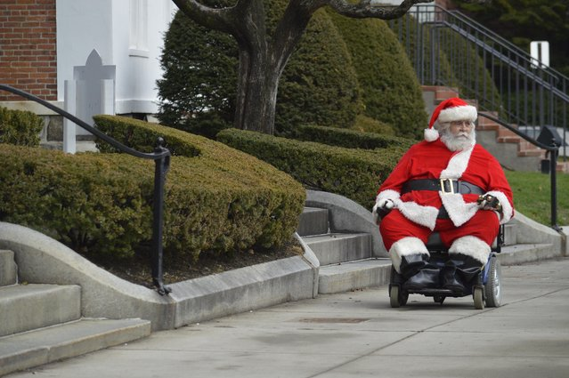 Ken Keefner, dressed as Santa, rides his wheelchair on Park Square in Pittsfield, Mass., Wednesday, December 23, 2015. Record warmth was expected on Christmas Eve along the East Coast, said Bob Oravec, lead forecaster with the National Weather Service. (Photo by Ben Garver/The Berkshire Eagle via AP Photo)