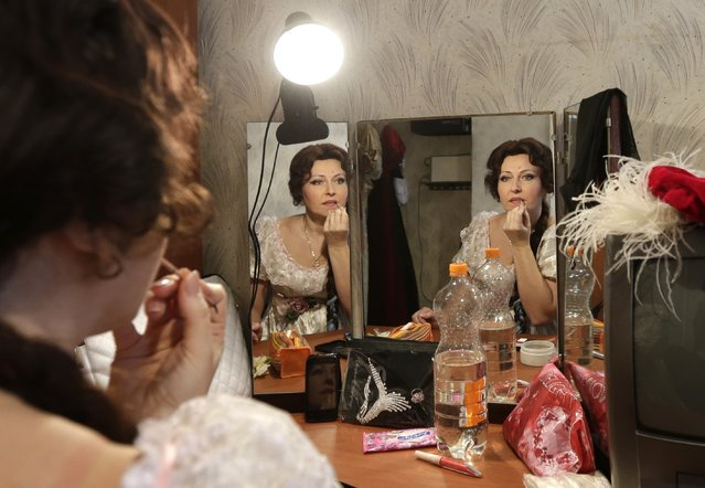 Actress with the Donbass Opera Theatre prepares to perform Eugene Onegin in Donetsk, Ukraine, Saturday, February 7, 2015. For the few dozen spectators that turn up, the weekly performances at the city's opera house serve as a respite from the war raging outside between Russian-backed separatists and Ukrainian government forces. (Photo by Petr David Josek/AP Photo)