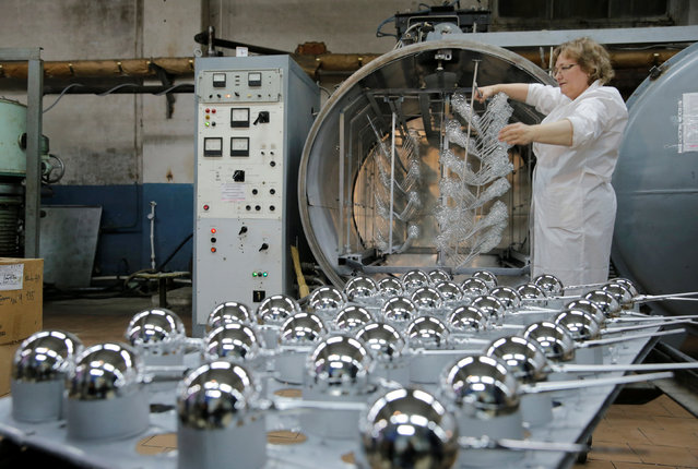 """An employee adjusts glass spheres for Christmas and New Year decorations in a spraying chamber before coating them with a layer of aluminum at the """"Yolochka"""" (Christmas tree) factory, which has been producing glass decorations and toys for the festive season since 1848, in the town of Klin outside Moscow, Russia, November 24, 2016. (Photo by Maxim Zmeyev/Reuters)"""