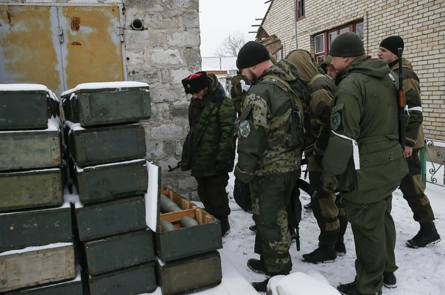 Pro-Russian separatists inspect boxes with ammunition used by Ukrainian government troops in the town of Vuhlehirsk, eastern Ukraine February 10, 2015. (Photo by Maxim Shemetov/Reuters)