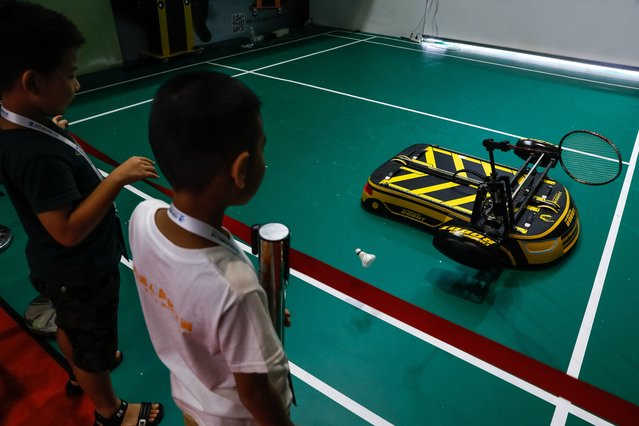 Chinese children look at a robot playing badminton during the 2018 World Robot conference in Beijing, China, 15 August 2018. (Photo by Roman Pilipey/EPA/EFE/Rex Features/Shutterstock)