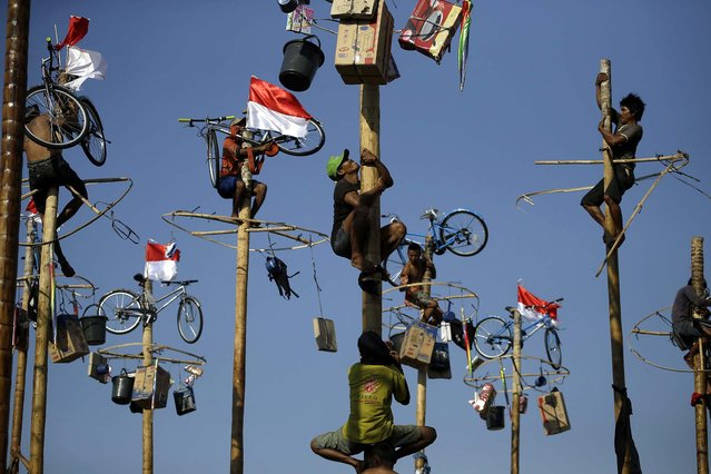 Participants struggle during a greased pole climbing competition held during Independence Day celebrations at Jaya Ancol Dream Park in Jakarta, on August 17, 2013. Indonesia is celebrating its 68th anniversary of independence from Dutch colonial rule. (Photo by Dita Alangkara/Associated Press)