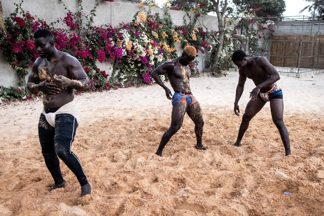 Senegalese wrestlers cover themselves in sand as they prepare to start their training program in Petit Mbao on March 29, 2021. As Covid-19 restrictions have been lifted, wrestlers now start prepare themselves for the start of wrestling tournaments. Senegalese wrestling, which has its roots in the ceremonies celebrating the end of harvests in Serer and Diola ethnic groups and remains surrounded by a thick cloud of mystical practice, is still extremely popular in this West African country. (Photo by John Wessels/AFP Photo)