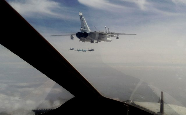 """Russian Air Force Su-24 bombers (center) fly during a military exercise in southern Russia on February 11, 2015. Marathon talks in Belarus ended on February 12 with a ceasefire announcement in the war between Ukraine and pro-Moscow rebels, but Germany's Chancellor Angela Merkel warned that """"big hurdles"""" remained. (Photo by Sergey Venyavsky/AFP Photo)"""
