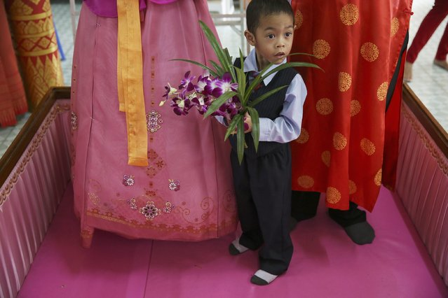 Sibb, 3, holds flowers between his parents standing in a pink coffin during their wedding ceremony at Wat Takien temple in Nonthaburi province, on the outskirts of Bangkok February 14, 2015. (Photo by Damir Sagolj/Reuters)