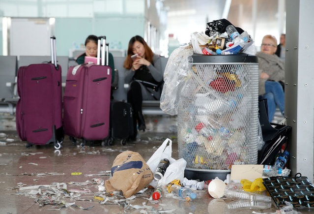 Passengers check their mobile devices as a bin is full of garbage during a protest by the cleaning staff at Barcelona's airport, Spain, December 1, 2016. (Photo by Albert Gea/Reuters)