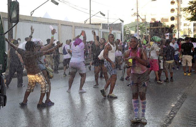 """A reveller protects his drink as it rains during Jouvert, part of Carnival in Saint James, Port of Spain February 16, 2015. Jouvert originates from the French phrase """"jour ouvert"""", meaning daybreak or morning, and signals the start of Carnival. (Photo by Andrea De Silva/Reuters)"""