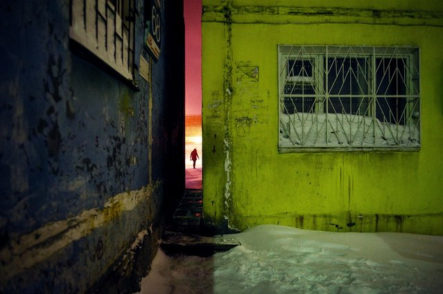 2013. A woman is visible through a narrow passageway between two buildings. Norilsk's urban spaces were designed to shorten distances around large developments and give residents maximum protection from arctic winds. (Photo by Elena Chernyshova)