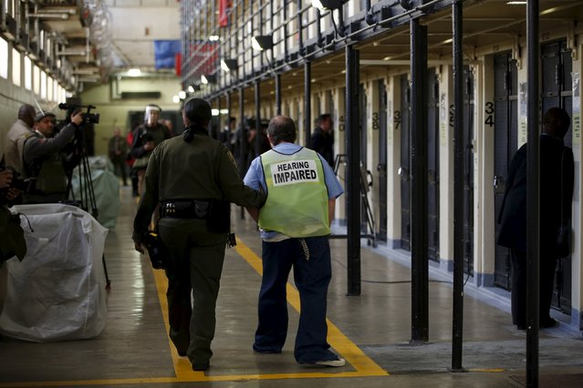 A guard escorts a hearing-impaired inmate down a corridor in the East Block during a media tour of California's Death Row at San Quentin State Prison in San Quentin, California December 29, 2015. (Photo by Stephen Lam/Reuters)