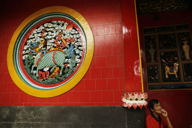 A man smokes a cigarette as he sits at Petak Sembilan temple, which is making preparations for the upcoming Chinese Lunar New Year, in Jakarta February 17, 2015. (Photo by Reuters/Beawiharta)