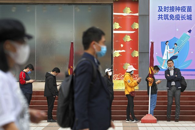 """People wearing face masks to help curb the spread of the coronavirus walk by masked residents lining up for COVID-19 vaccine at a vaccination site with a board displaying the slogan, """"Timely vaccination to build the Great Wall of Immunity together"""" in Beijing, Wednesday, April 21, 2021. (Photo by Andy Wong/AP Photo)"""