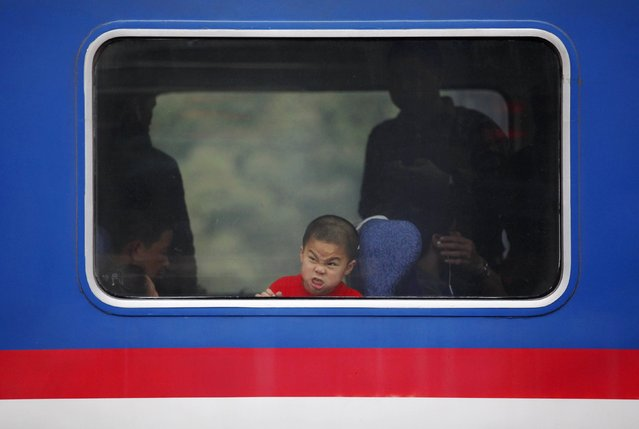 A boy makes faces as he looks out a window of a train at a railway station in Huizhou, Guangdong province February 11, 2015. The Chinese Ministry of Transport said a total of 2.807 billion trips are expected to be made during the 40-day Spring Festival travel rush, which will begin on February 4 and last until March 16, Xinhua News Agency reported. (Photo by Reuters/Stringer)