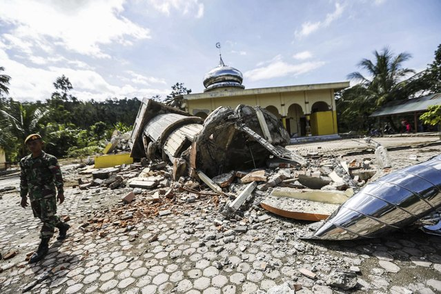 An Indonesian soldier inspects a collapsed mosque after an earthquake struck Pidie Jaya, Aceh, Indonesia, 07 December 2016. According to media reports at least 52 people were killed after a strong quake rocked Aceh in the early morning of 07 December. According to the United States Geological Survey (USGS), the shallow 6.5 magnitude earthquake struck Aceh province of Sumatra island. No tsunami alert was issued in the wake of the earthquake. (Photo by Hotli Simanjuntak/EPA)
