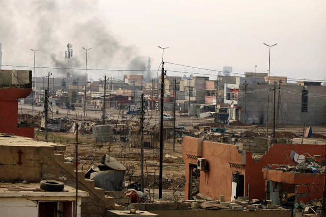 Smoke from clashes during a battle with Islamic State militants is seen rising behind damaged buildings in Mosul, Iraq, December 5, 2016. (Photo by Thaier al-Sudani/Reuters)