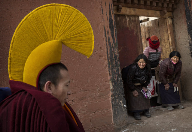 Devotees bow to a passingTibetan Buddhist monk on his way to take part in a special prayer during Monlam or the Great Prayer rituals on March 5, 2015 at the Labrang Monastery, Xiahe County, Amdo, Tibetan Autonomous Prefecture, Gansu Province, China. (Photo by Kevin Frayer/Getty Images)