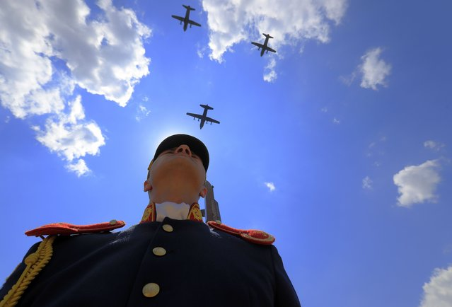 A Romanian honor guard soldier stands still as three military aircraft carriers are crossing the sky during a ceremony held at the Unknown Soldier Memorial, in Carol I Park, on the occasion of the Heroes' Day commemoration, in Bucharest, Romania, 10 June 2021. (Photo by Robert Ghement/EPA/EFE)