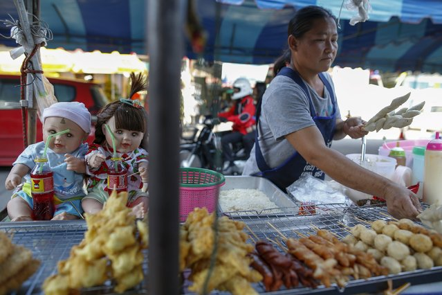 "Hong, 42, a street food stall owner, works next to her ""child angel"" dolls near Wat Bua Khwan temple in Nonthaburi, Thailand, January 26, 2016. (Photo by Athit Perawongmetha/Reuters)"