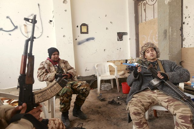Members of the Libyan pro-government forces, who are backed by the locals, take a break during street clashes with the Shura Council of Libyan Revolutionaries, an alliance of former anti-Gaddafi rebels who have joined forces with the Islamist group Ansar al-Sharia, in Benghazi March 16, 2015. (Photo by Esam Omran Al-Fetori/Reuters)