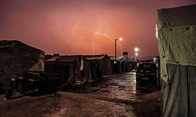 Lighting strikes above tents at a camp for diplaced people near the town of Deir al-Ballut in Afrin's countryside, in Syria's Aleppo province near the border with Turkey, on January 13, 2021. (Photo by Rami Al Sayed/AFP Photo)