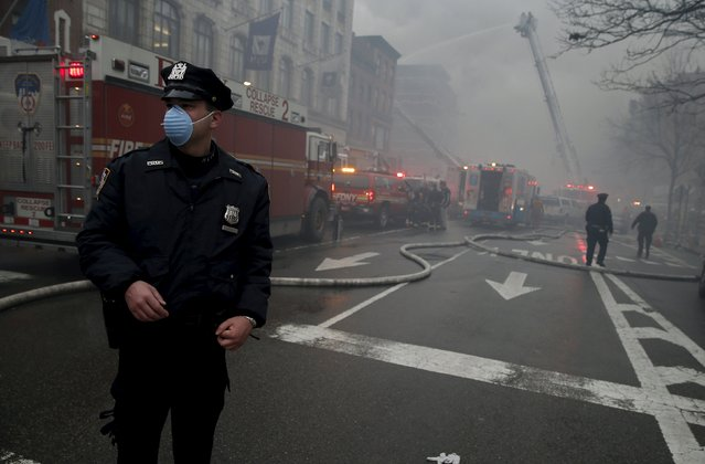 A New York City Police officer wears a mask as he stands near the site where a residential apartment building collapsed and was engulfed in flames in New York City's East Village neighborhood March 26, 2015. (Photo by Mike Segar/Reuters)