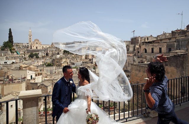 """Just married Alberto and Lucia pose for photographers with """"Sassi di Matera"""" districts on the background, in Matera, Italy, June 29, 2021. (Photo by Yara Nardi/Reuters)"""