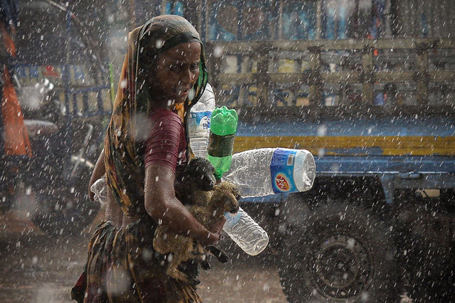 A woman seeks shelter during a downpour in Dhaka on June 21, 2021. (Photo by Munir Uz Zaman/AFP Photo)