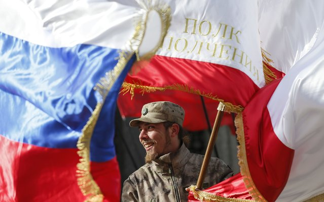 A member of the People's Militia of Crimea reacts during a ceremony, marking the first anniversary of the Crimean referendum to secede from Ukraine and join Russia, in Simferopol, March 16, 2015. Many members of the current militia joined local pro-Russian self-defence units more than a year ago and were participants of the events, which resulted in Russia's annexation of Ukraine's Black Sea peninsula of Crimea. (Photo by Maxim Shemetov/Reuters)