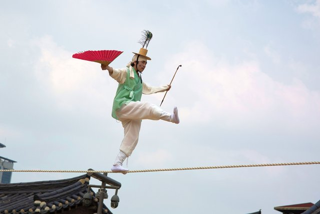 """South Korean tightrope walker Nam Chang-dong performs """"Jultage"""" or Tightrope walking during the traditional festival """"Dano"""" at Namsan Hanok village in Seoul, South Korea, 14 June 2021. The festival falls on the fifth day of the fifth month of the lunar calendar. Only 30 audience members were allowed to attend the performance amid the coronavirus COVID-19 pandemic. (Photo by Jeon Heon-Kyun/EPA/EFE)"""