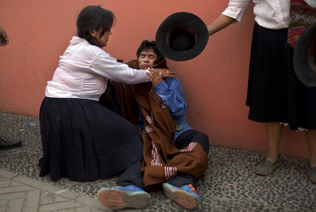 In this Sunday, March 29, 2015 photo, women assist a fellow performer who was overcome by alcohol and exhaustion after he danced a thirty minute traditional dance in the Vencedores de Ayacucho dance festival, at the Acho bullring in Lima, Peru. There is dancing from sunup to sundown in the one-day competition, in Latin America's oldest bullring. (Photo by Rodrigo Abd/AP Photo)