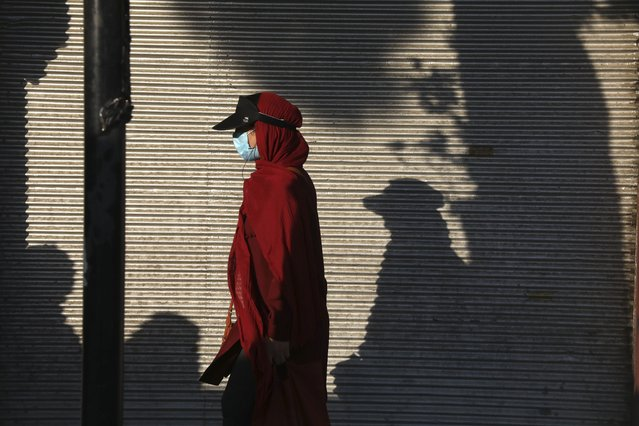 A woman wearing protective face mask to help prevent the spread of the coronavirus walks on a sidewalk in southern Tehran, Iran, Tuesday, July 20, 2021. Iran on Tuesday broke another record in the country's daily new coronavirus cases, even as Tehran and its surroundings went into lockdown, a week-long measure imposed amid another surge in the pandemic. (Photo by Vahid Salemi/AP Photo)
