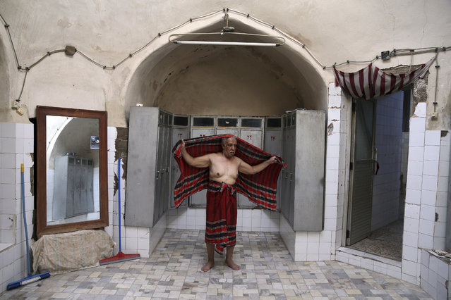 In this Friday, November 21 2014 photo, Ali Tayyeb, 70, a bathhouse worker, drys himself at the end of his workday, at the Islam public bathhouse, in Yazd, Iran. (Photo by Ebrahim Noroozi/AP Photo)