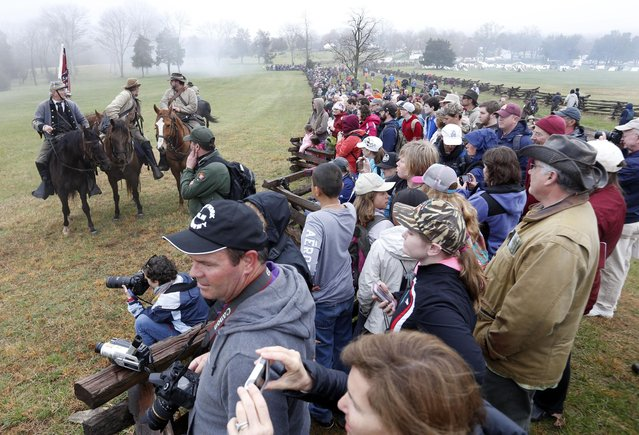 Confederate officers watch the battle along with visitors during a re-enactment of the Battle of Appomattox Courthouse as part of  the commemoration of the 150th anniversary of the surrender of the army of Northern Virginia at Appomattox Court House in Appomattox, Va., Thursday, April 9, 2015. (Photo by Steve Helber/AP Photo)