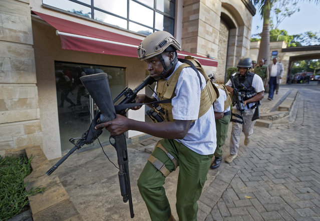 An armed member of Kenyan security forces runs through a hotel complex in Nairobi, Kenya Tuesday, January 15, 2019. Terrorists attacked an upscale hotel complex in Kenya's capital Tuesday, sending people fleeing in panic as explosions and heavy gunfire reverberated through the neighborhood. (Photo by Ben Curtis/AP Photo)