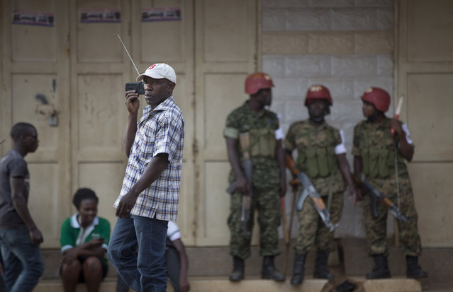 A man walks past listening to news on a portable radio as as military police deploy, shortly after the election result was announced, in downtown Kampala, Uganda, Saturday, February 20, 2016. (Photo by Ben Curtis/AP Photo)